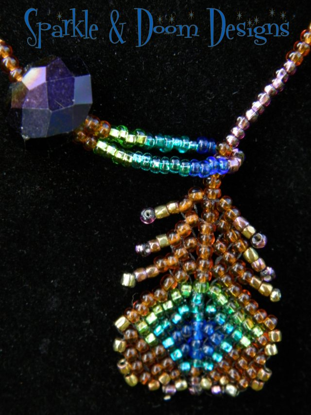 peacock feather lariet with purple oilslick crystal charm
