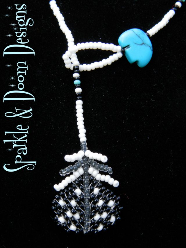 black with speckly white feather lariat with turquoise bear charm