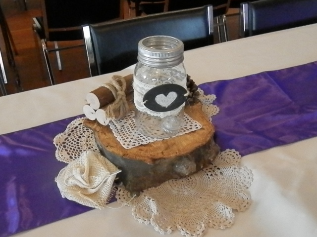 table decorations of wood slices, doilies, and mason jars with chalkboard hearts